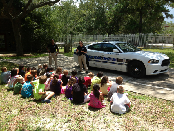 GPD Crime Prevention Team Officers addressing a group of small children outside.